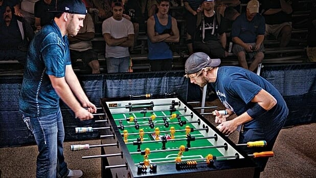 Two guys playing competitive foosball.