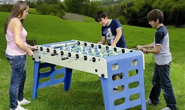 Kids playing outdoor foosball.