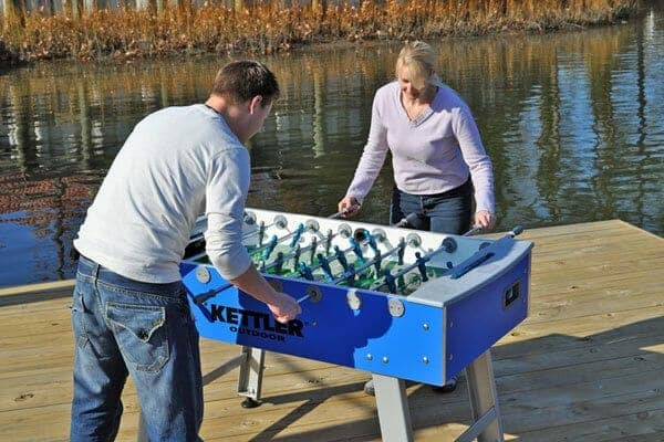 Two people playing outdoor foosball next to a body of water.