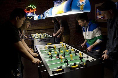 People playing foosball.